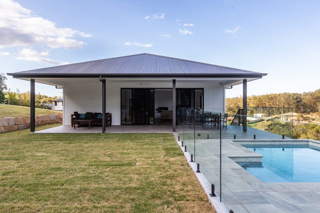 Outdoor entertaining area with pool and grassed area.